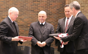 (From left) Brother James Gaffney, FSC, presents Brother Robert Schieler, FSC, with an honorary doctorate degree. Russ Smyth, Board Chair, and Brother Larry Schatz, FSC, Visitor of the Midwest District present the hood.Courtesy Lewis University